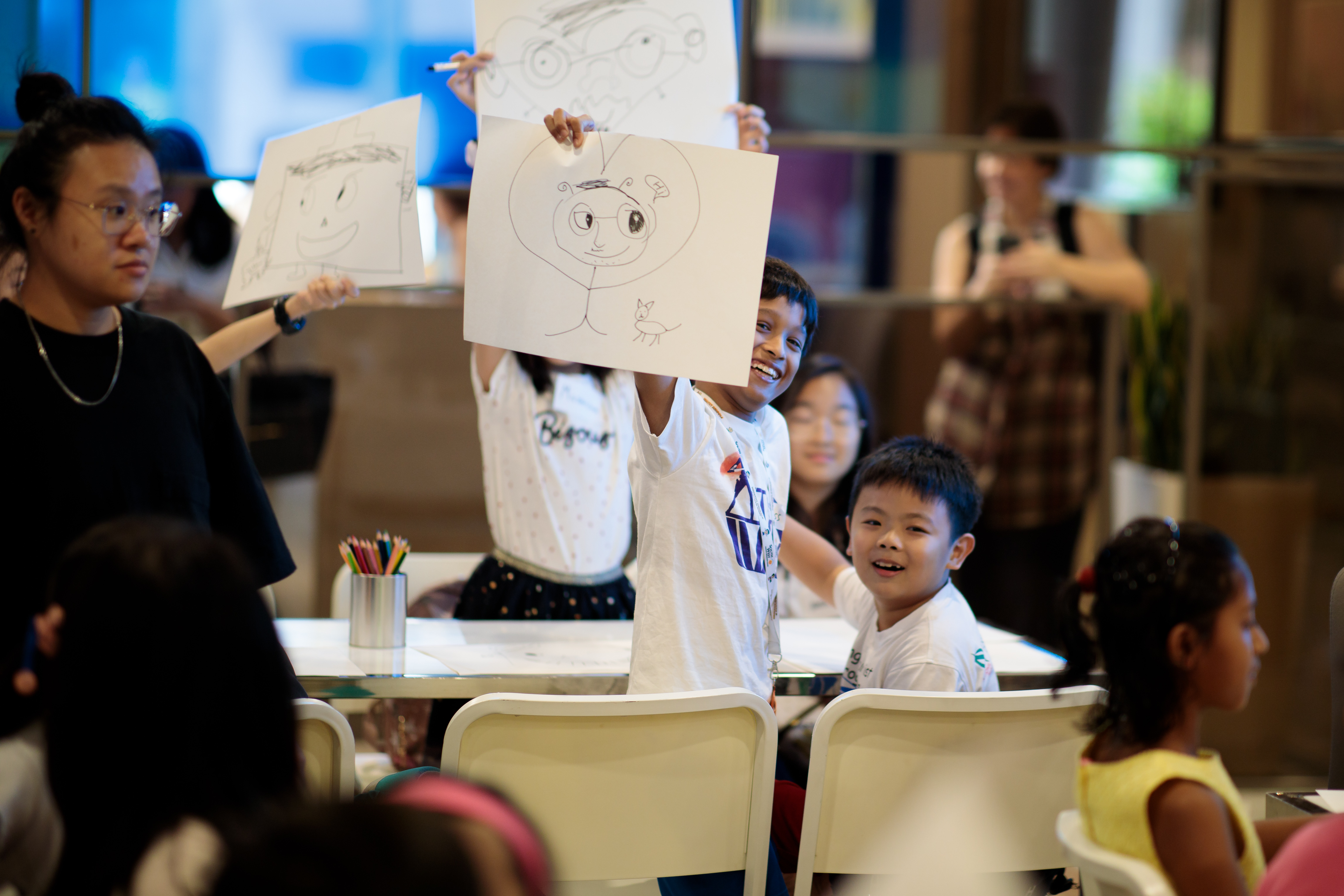 Proudly showing off his drawn creation to the rest of the class